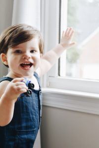 18 Month old Noah standing in front of a window. What's wrong?